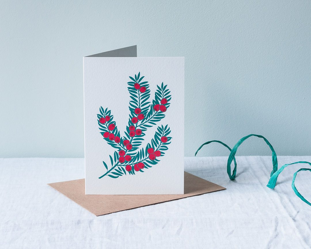 A Christmas card with an illustration of a yew branch